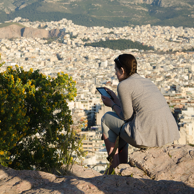 woman sitting on a ledge reading a tablet